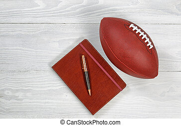 Playbook with Football on rustic white wood - Image of...