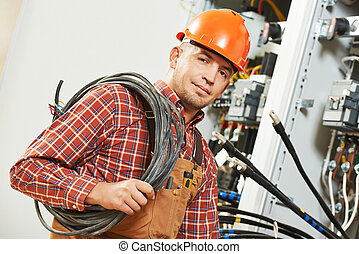 electrician engineer worker with cable in front of fuseboard...