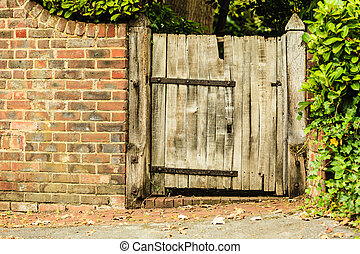 Rustic old wooden gate in brick wall - Countryside scene....
