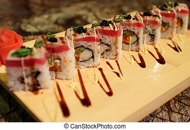 Delicious Sato maki sushi rolls served with a wood plate.