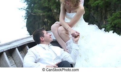 groom and bride talk and smooth hair in long tail boat -...