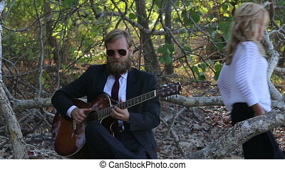 guitarist plays sitting on branch blonde girl stands at...