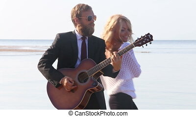 guitarist plays blonde girl dances near on beach against sea