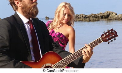 girl in dress with bow flirts dancing by guitarist on beach...