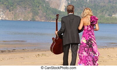 guitarist and blonde girl walk towards sea girl points to...