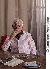 Lonely senior man smoking cigar and looking at old photos