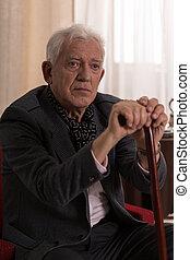 Man with walking stick - Aged sad injured man leaning on...