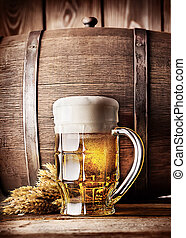 Faceted mug of light beer on a background of the old wooden...