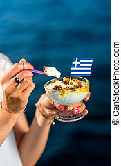 Greek yogurt with nuts and honey on blue sea background
