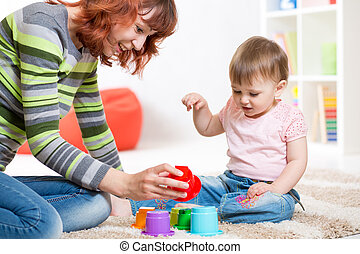 cute mother and her daughter playing together indoor - cute...