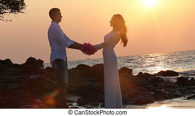 bride with bouquet comes to groom against rising sun -...