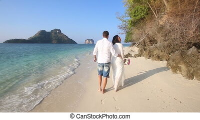 bride and groom walk barefoot along edge of water by cliffs