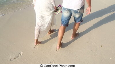 bride and groom walk barefoot along wet sand with footsteps...