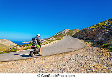 Man driving scooter on road turn in mountains - Man driving...