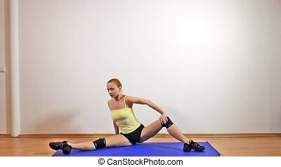 Slender athletic girl doing yoga exercises indoor stretching