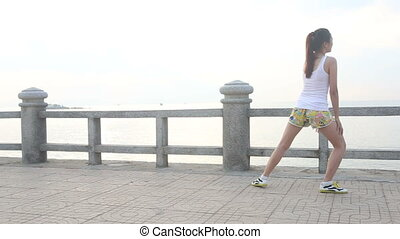 asian girl does exercises on embankment at dawn