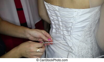 girl assistant ties corset to bride at back-side