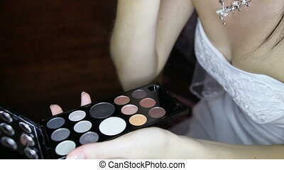 bride in wedding dress does makeup