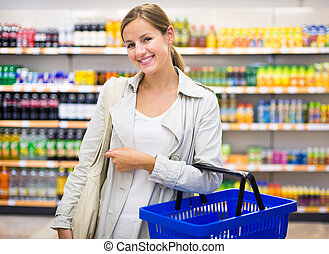 Pretty young woman buying groceries in a...