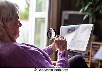Senior woman reading morning newspaper, sitting in her...