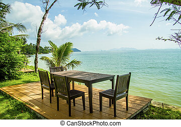Dining table prepared for two on white sand beach close to...
