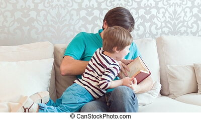 Dad and son in living-room - Give it to me. Laughing dad and...