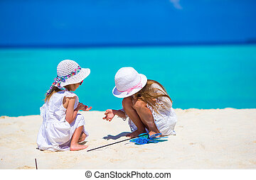 Little adorable girls drawing picture on white beach -...