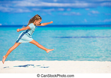 Adorable little girl running during beach vacation -...