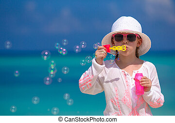 Adorable little girl making soap bubbles during summer...