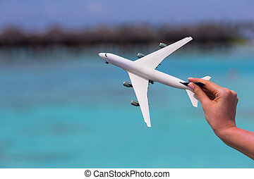 Little white toy airplane on background of turquoise sea -...