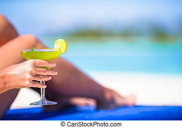 Young woman with tasty cocktail on beach loungers - Woman...