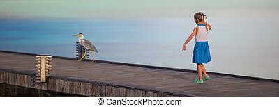 Adorable happy little girl with Grey heron on beach vacation...