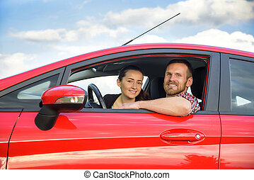 Couple in a red car - Two young smiling people in a red car