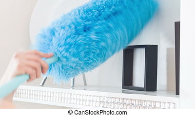 Work with blue duster - Dusting room in hotel. Charwoman...