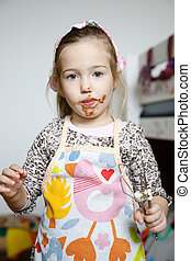 Little girl eating chocolate off the mixer beater after...