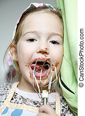 Little girl licking chocolate off the mixer beater after...