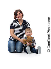young beautiful mother in jeans sitting with her son three years on the floor