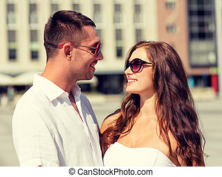 smiling couple in city - love, travel, tourism, people and...