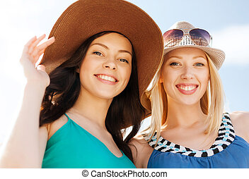 girls in hats on the beach - summer holidays and vacation...