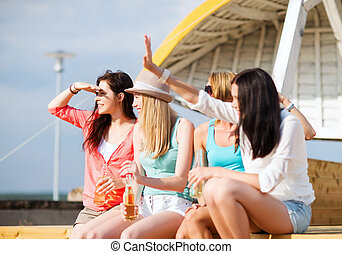 girls with drinks on the beach - summer holidays and...