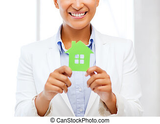 african woman holding green paper house