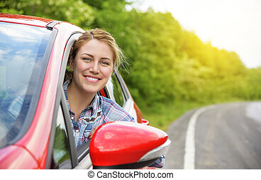 Woman in red car. - Happy smiling girl in a red car. At...
