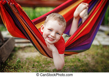 Beautiful cheerful little boy resting in a hammock and...