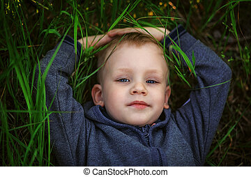 Portrait of a smiling little boy lying on green grass -...