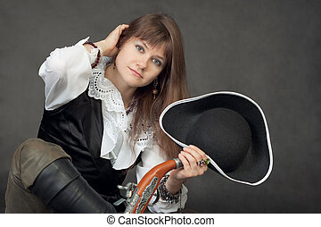Young beautiful woman in costume of pirate on black background