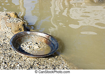 Gold Pan by the River - A well-used gold pan sits idle on...