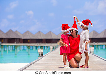 Young mother and little girls in Santa hat at tropical beach