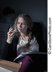 Woman working and drinking alcohol