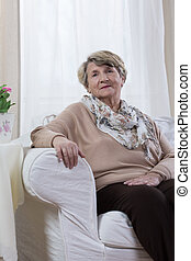 Calm elderly lady sitting alone in her room