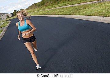 Beautiful Blond Woman Running and Listening to MP3 Player -...